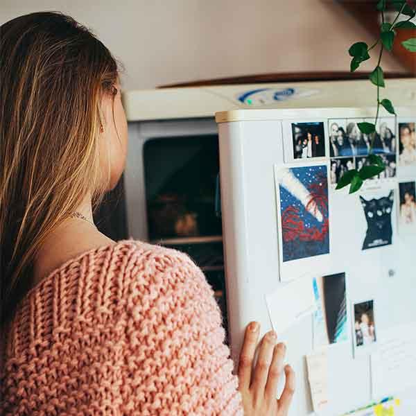 Preserving freezer leftovers - Women looking in fridge and freezer.