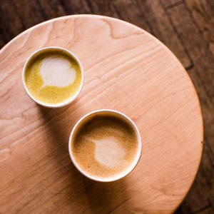 Two mugs sitting on a wooden table, containing drinks made with turmeric.