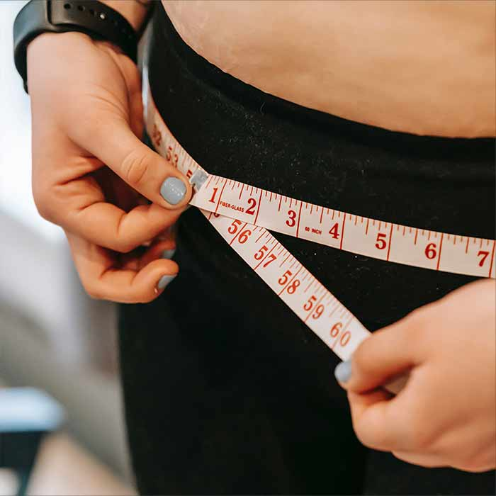 Obese women measuring her waist line